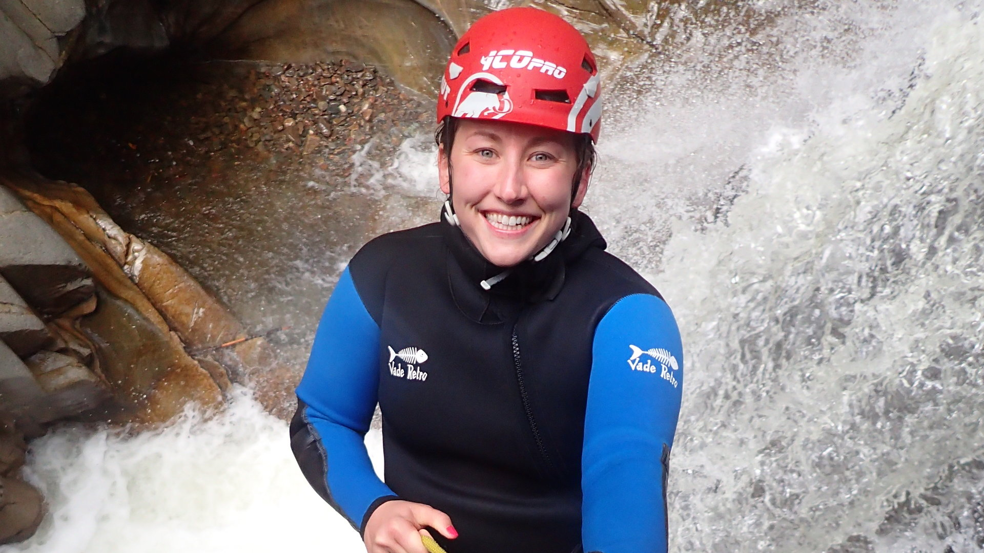 canyoneer smiling as they abseil down a waterfall
