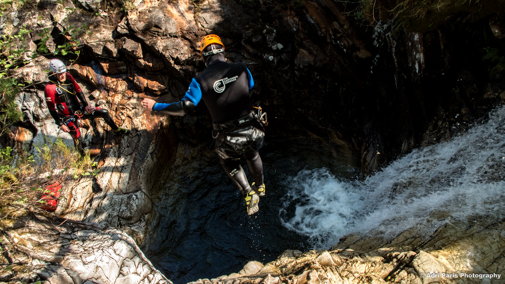 canyoneer jumping off cliff into water