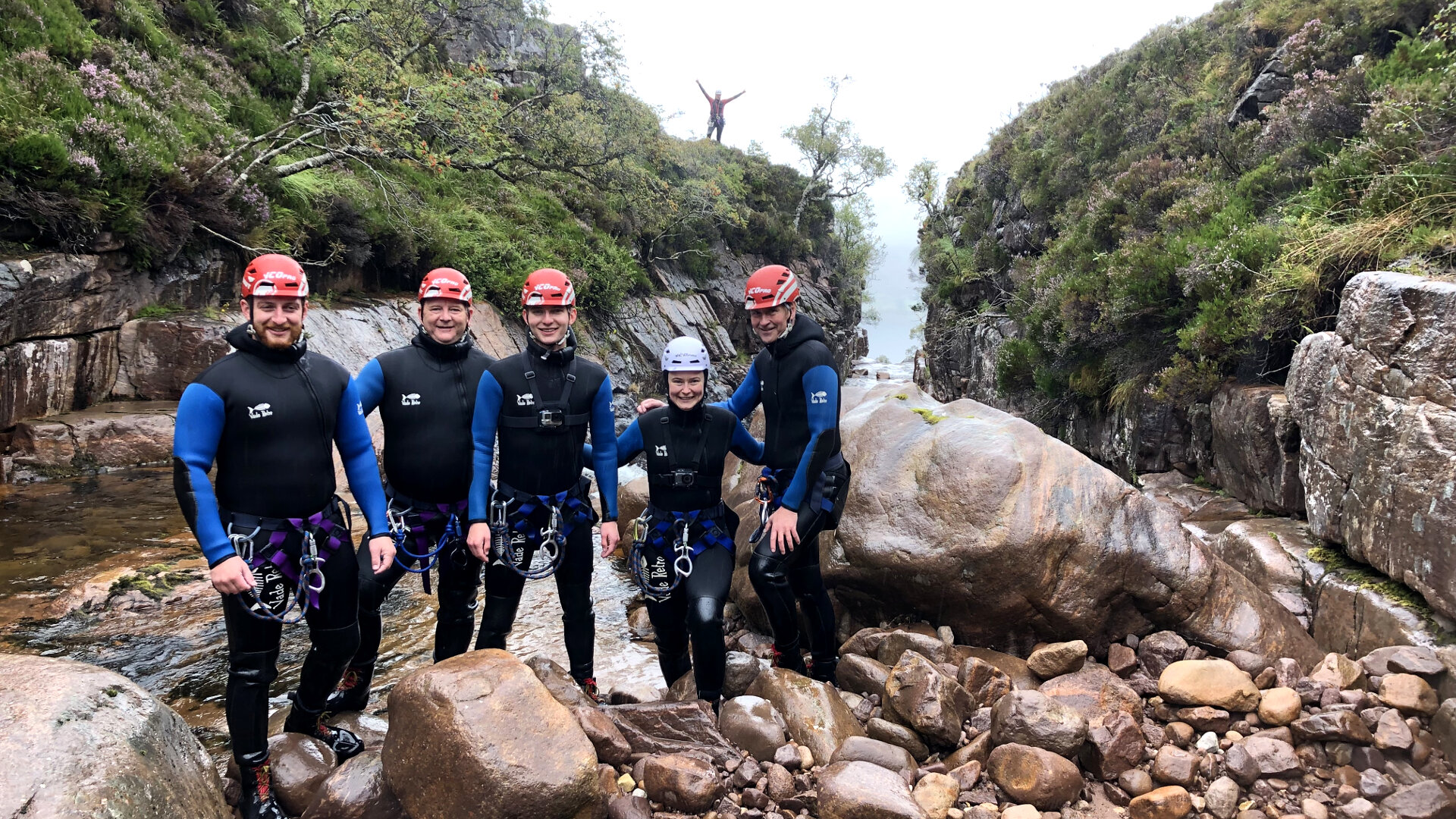 team of canyoneers at base of waterfall