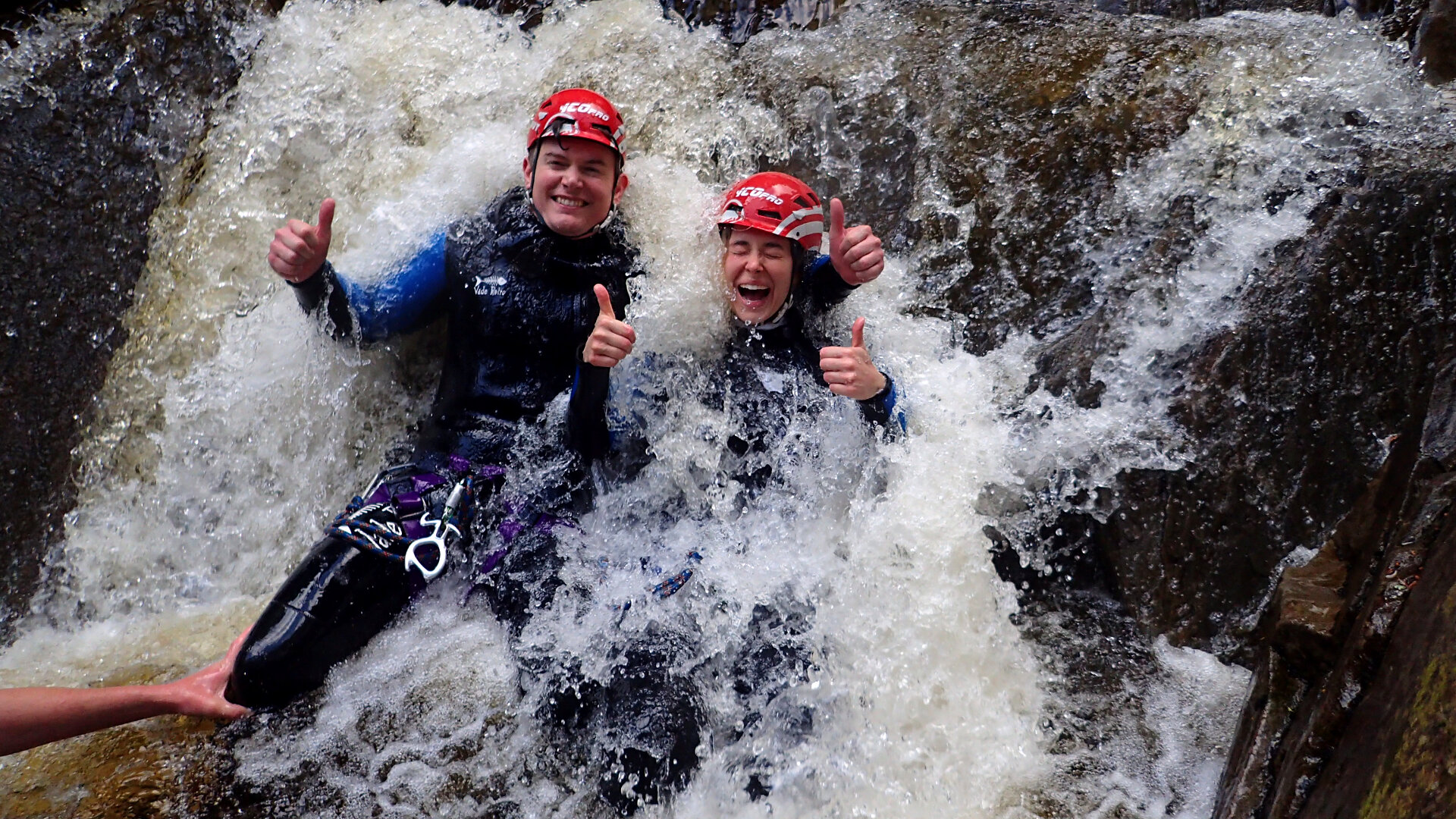two people sitting underneath flowing waterfall with water splashing over them
