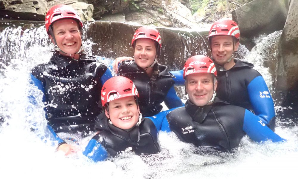 Famil in water at base of waterfall on gorge walking trip