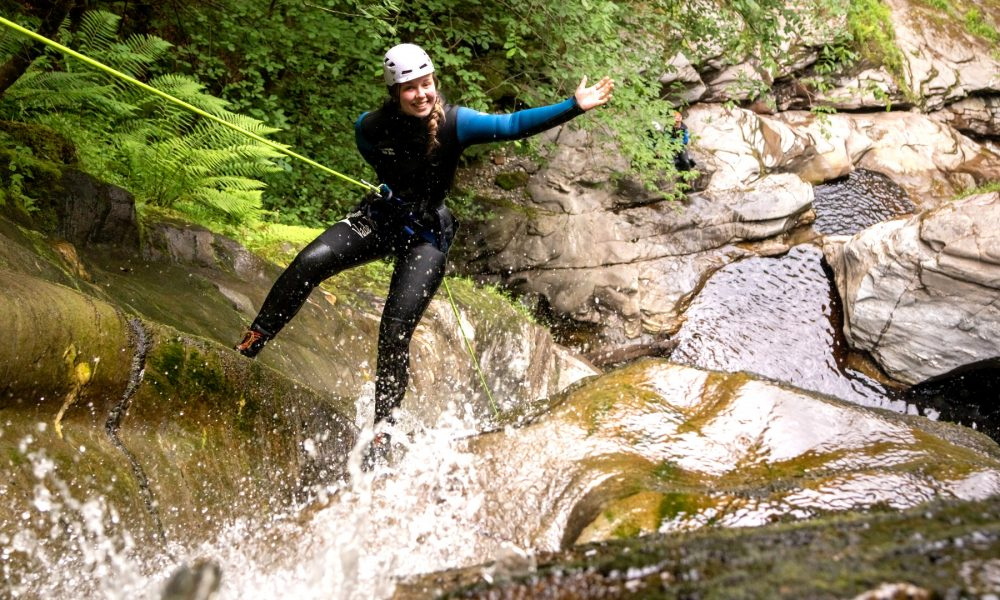 Girl abseiling and repelling down waterfall at acharn canyon
