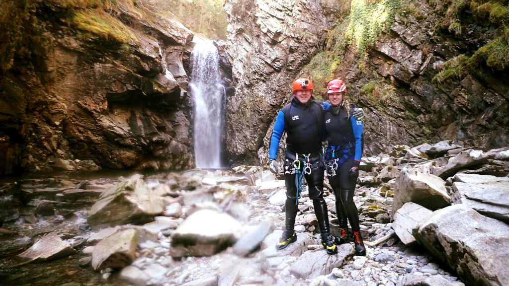 Man and woman Standing near bottom of waterfall