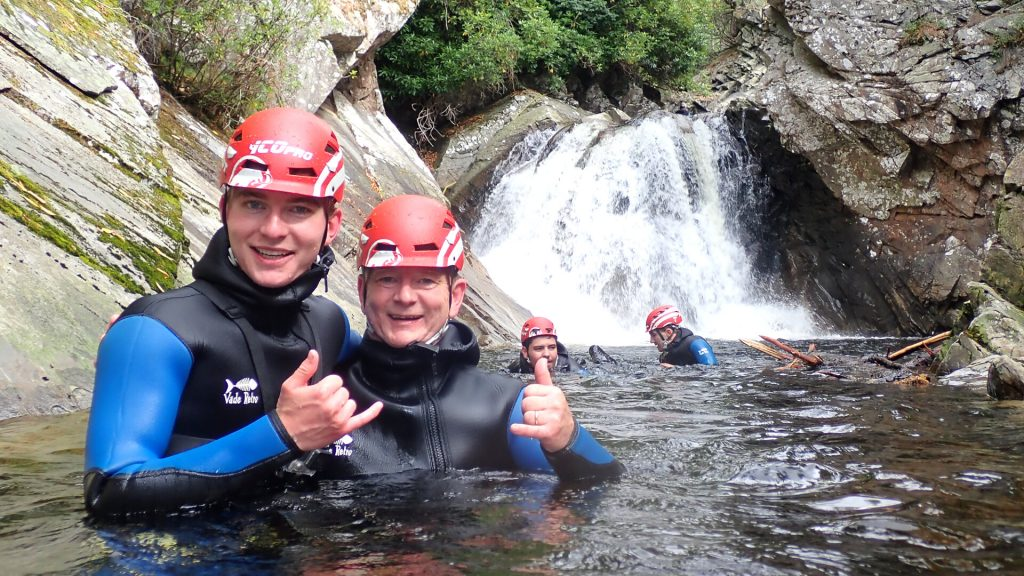 Two Men Chest Deep In Water Walking Through Gorge