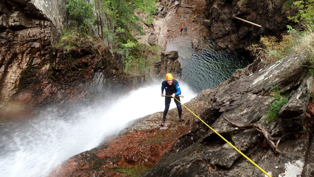 Canyoneer abseiling down large cliff and waterfall at grey mares
