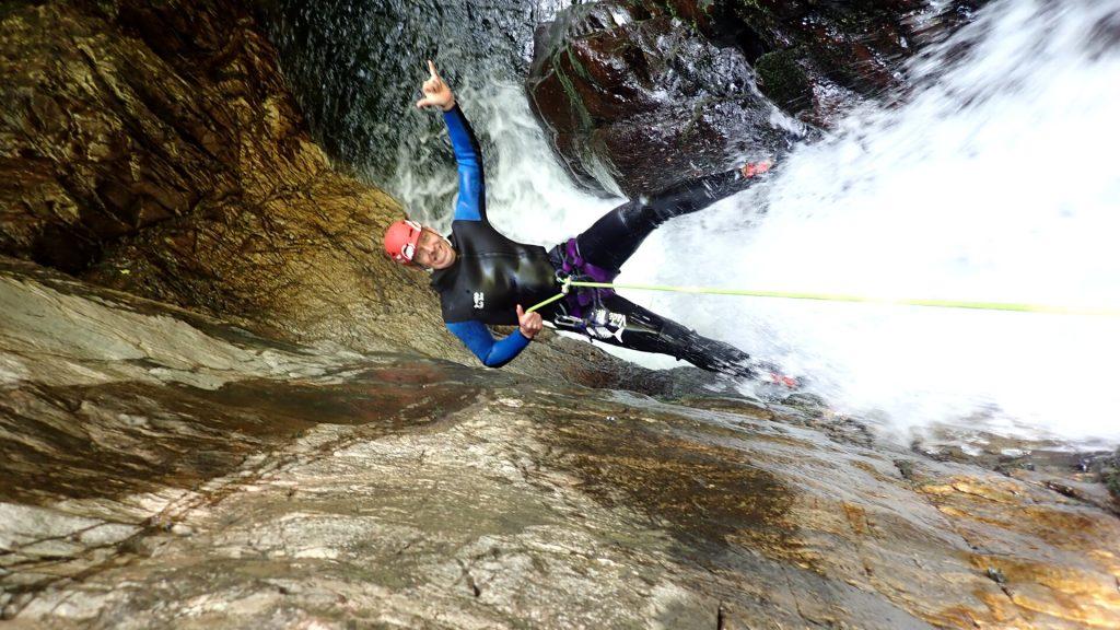 canyoneer rappelling down waterfall