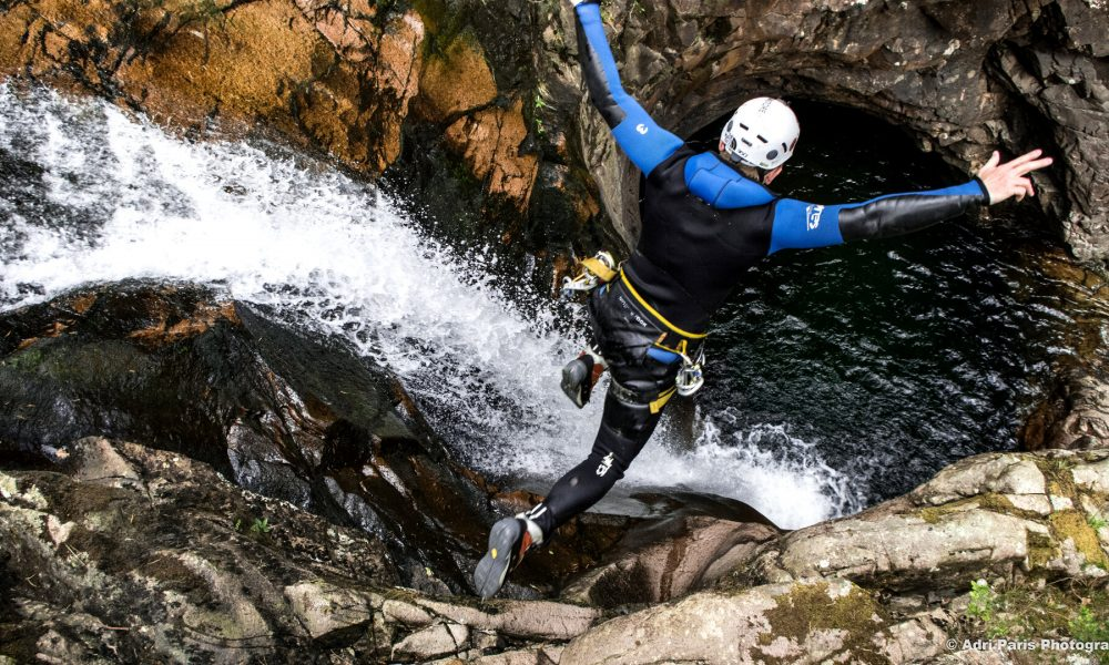 Canyoneer jumping into plunge pool on canyoning trip