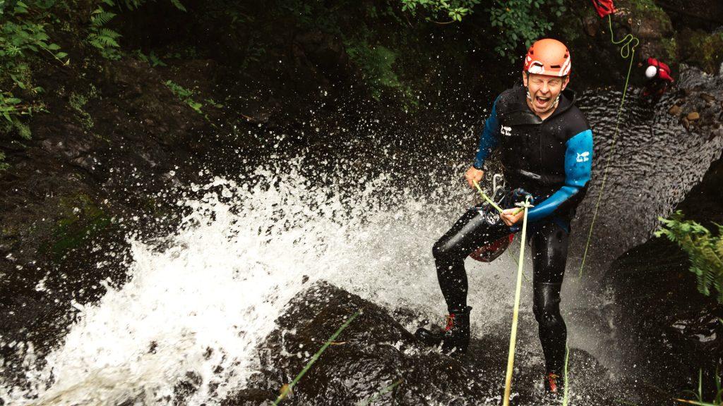 canyoneer abseiling down waterfall