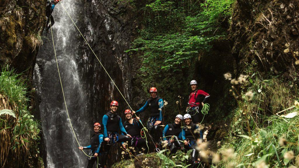 Canyoning group at bottom of waterfall