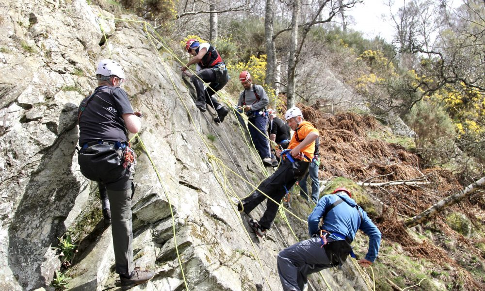 Canyoning training expedition in Scotland abseiling down cliff