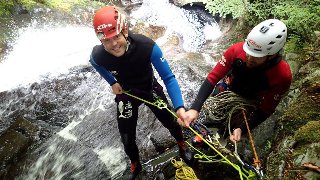 Canyoneer rapel over cliff waterfall
