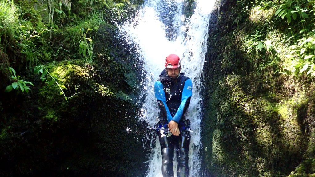 canyoneer sliding down natural water slide