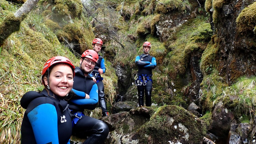 Team of gorge walkers smiling as they walk through gorge
