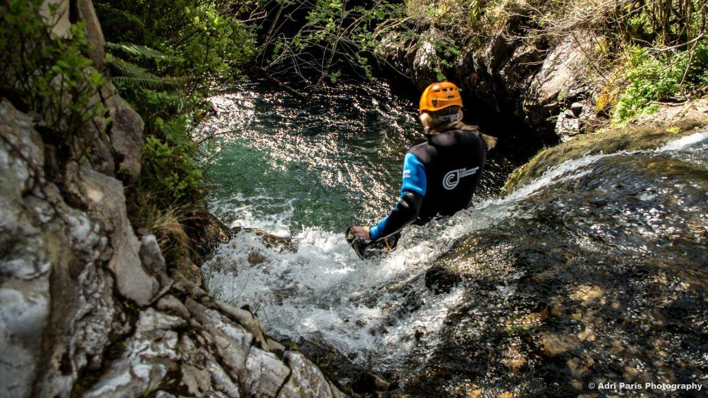 canyoneer sliding down natural water flume