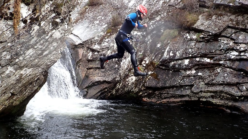 canyoneer jumping into water off of a cliff