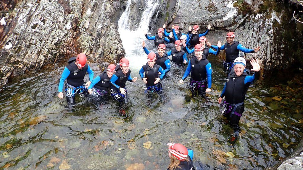 team of canyoneers resting waist deep in water