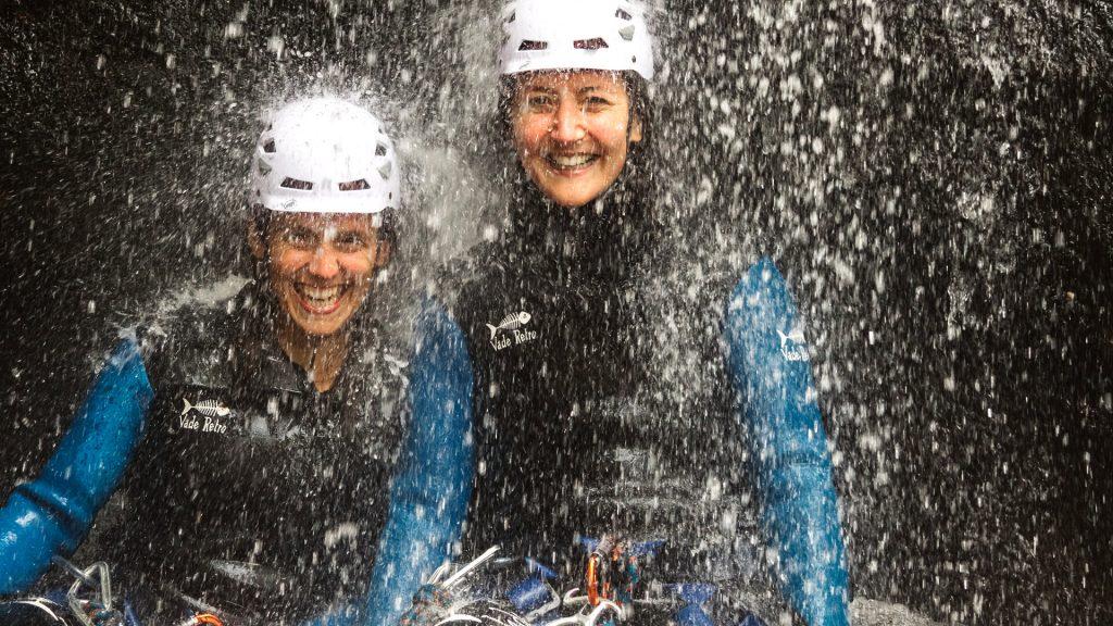 girls smiling underneath waterfall