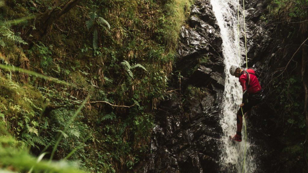 canyoneer descending waterfall by rope