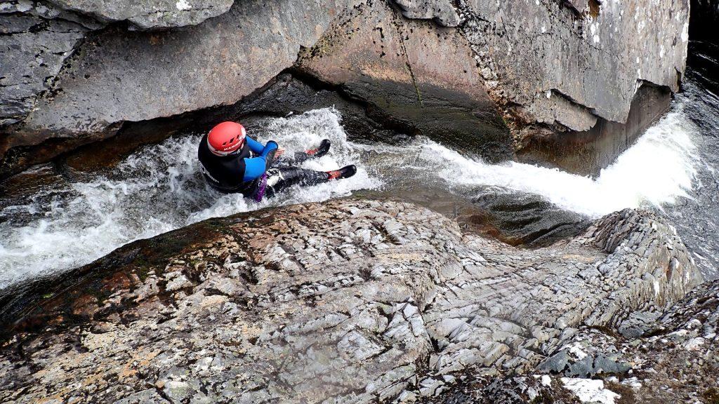 Canyoneer sliding down natural rock water slide