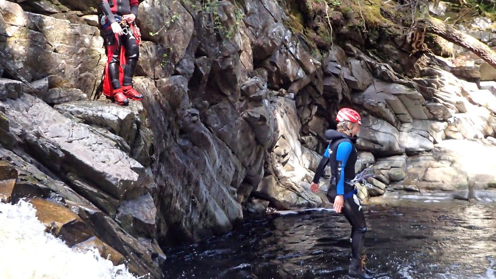 canyoneer jumping into plunge pool